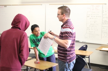 A Davidson Academy teacher interacting with two students in the classroon