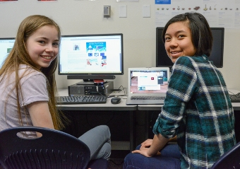 Two gifted students smiling while on computers in a Davidson Academy classroom