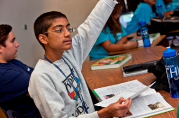 A gifted student raising his hand in the classroom