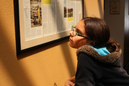 A gifted student viewing a display of media featuring the Davidson Institute