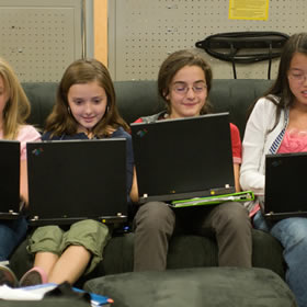 a few gifted students smiling as they work on laptops
