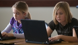 two gifted students concentrating while working on laptops