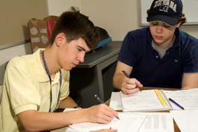 Gifted students writing while working on assignments in a classroom