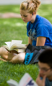 A gifted student on the lawn reading her book